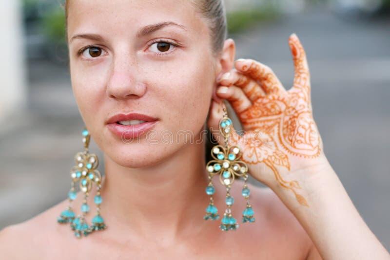 Femme avec le tatouage et la boucle d'oreille de henné photographie stock libre de droits