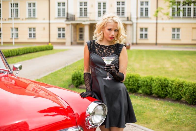 Femme avec le verre de cocktail se tenant à côté de la rétro voiture images libres de droits