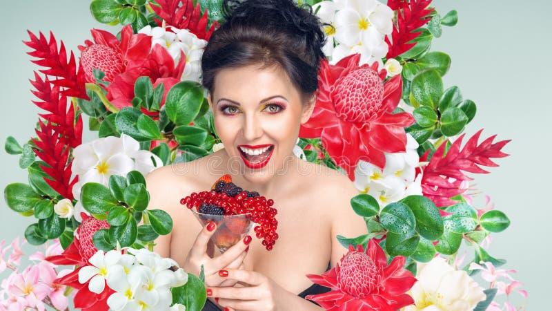 Femme avec le verre de fruits et de baies devant le fond de fleurs photographie stock libre de droits