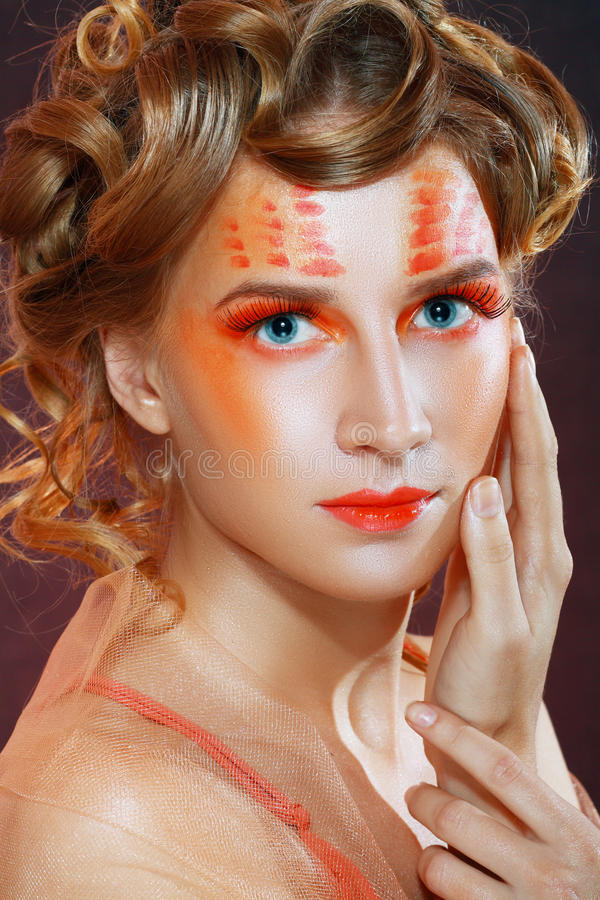 Femme avec le visage artistique orange photos stock