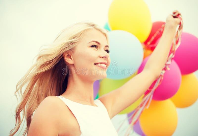 Femme avec les ballons colorés dehors image stock