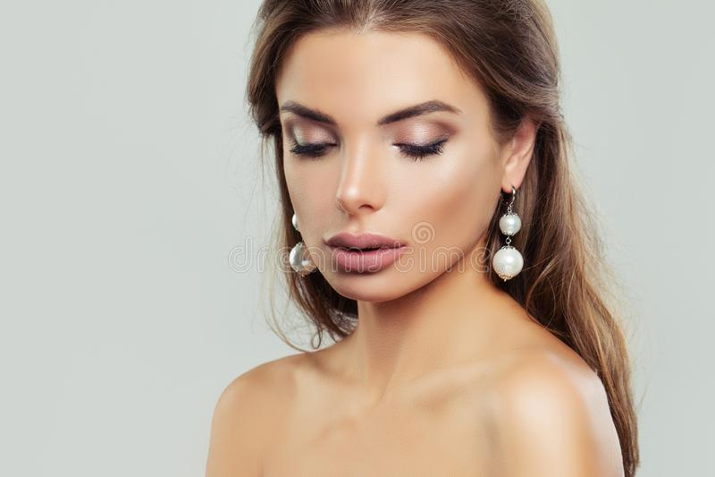 Femme avec les boucles d'oreille parfaites de maquillage et de perles image stock