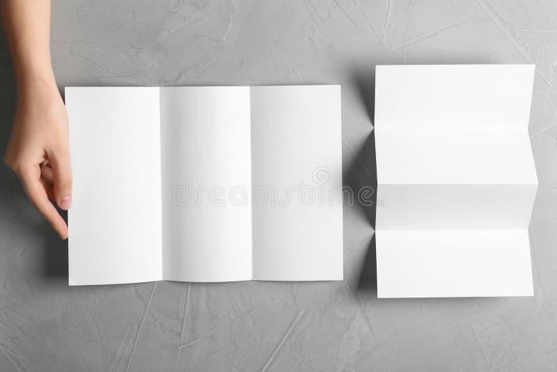 Femme avec les brochures vides sur le fond gris, vue supérieure images libres de droits