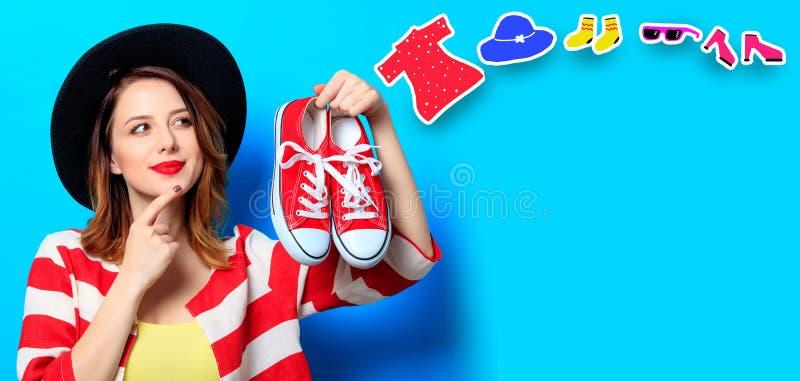 Femme avec les chaussures en caoutchouc et les vêtements rouges images stock