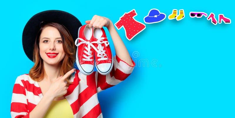 Femme avec les chaussures en caoutchouc et les vêtements rouges image stock
