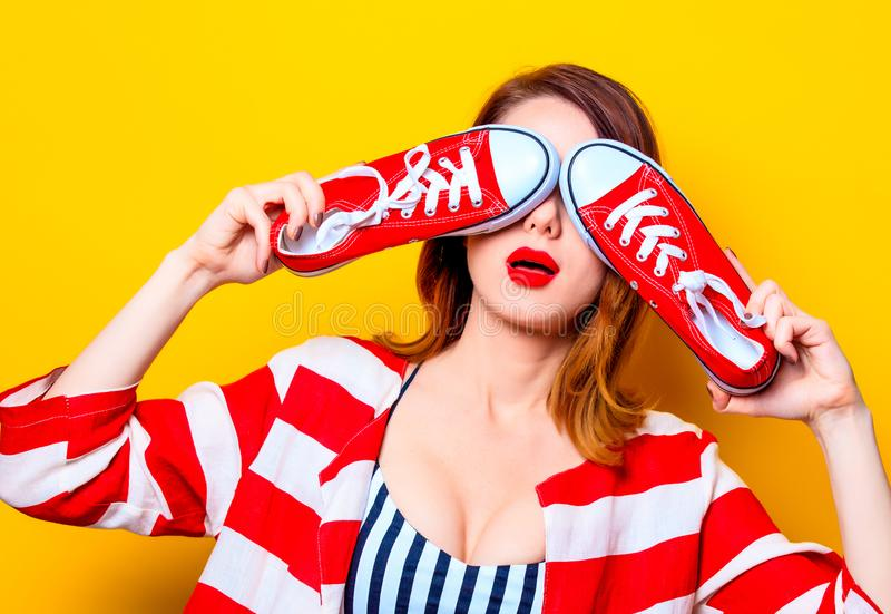Femme avec les chaussures en caoutchouc rouges image stock