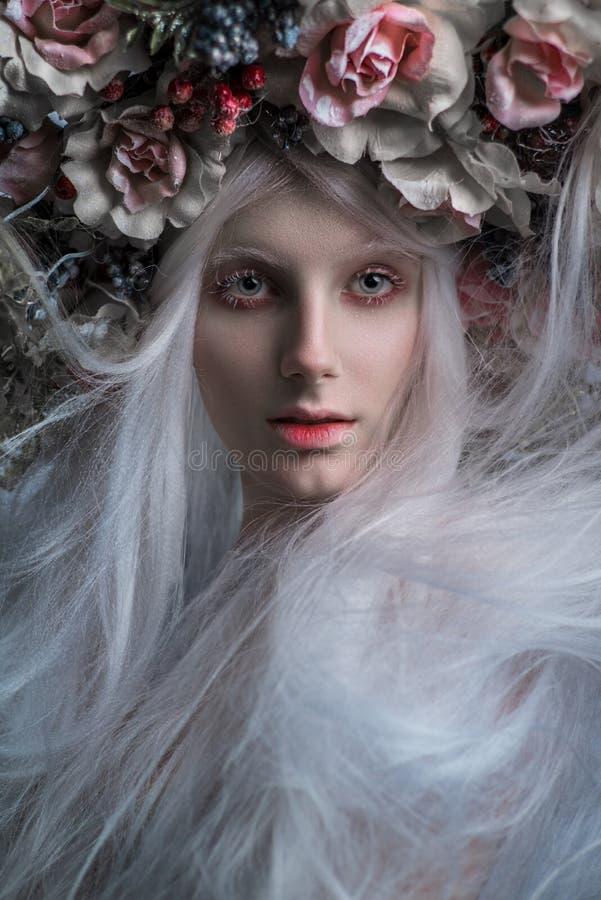Femme avec les cheveux blancs et les roses blanches et la neige image libre de droits