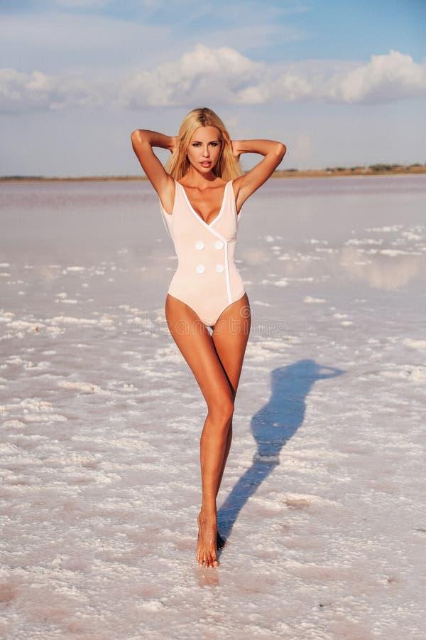 Femme avec les cheveux blonds dans le costume de natation élégant presque posant images stock