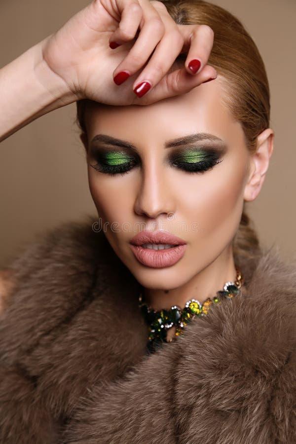 Femme avec les cheveux blonds et le maquillage lumineux, dans le manteau de fourrure élégant avec le bijou photos libres de droits