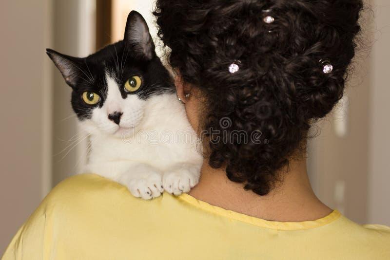 Femme avec les cheveux bouclés tenant le chaton noir et blanc domestique avec les yeux verts Concept de l'amour aux animaux, anim images libres de droits