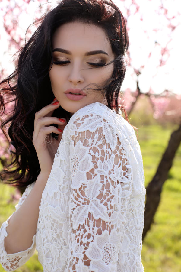 Femme avec les cheveux foncés dans la robe élégante posant dans le jardin de fleur photo stock