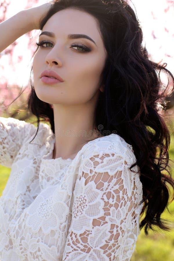 Femme avec les cheveux foncés dans la robe élégante posant dans le jardin de fleur photographie stock libre de droits
