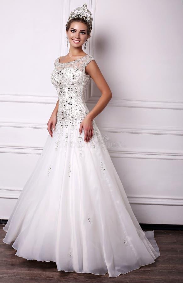 Femme avec les cheveux foncés dans la robe de mariage luxueuse et la couronne précieuse photographie stock