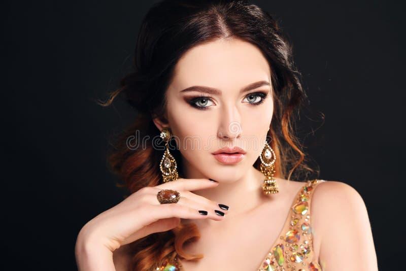 Femme avec les cheveux foncés portant la robe et le bijou luxueux de paillette image stock