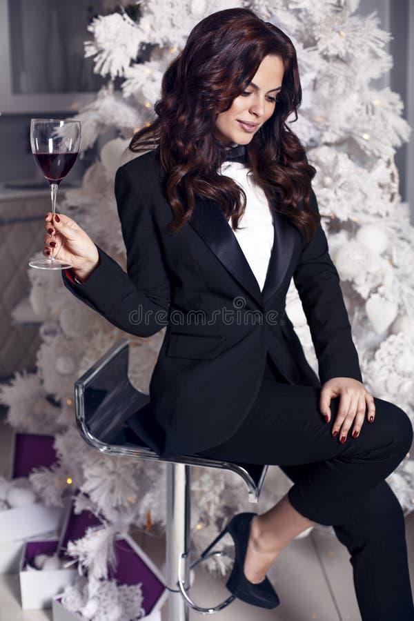 Femme avec les cheveux foncés portant le costume noir élégant, tenant un verre de vin photos libres de droits