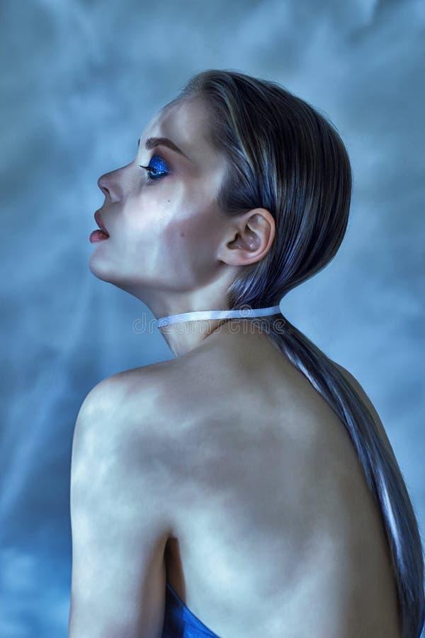 Femme avec les cheveux humides et le maquillage lumineux posant près de l'eau, portrait Brillez de l'eau sur le visage de fille,  images libres de droits