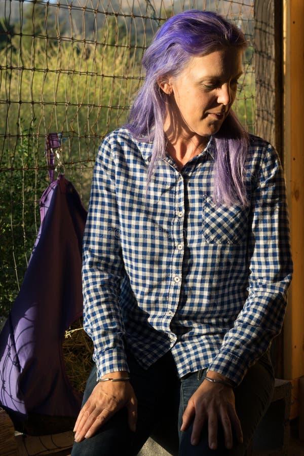 Femme avec les cheveux pourpres se reposant dans un abri de chèvre images stock