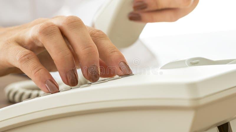 Femme avec les clous vernis composant à un téléphone image stock