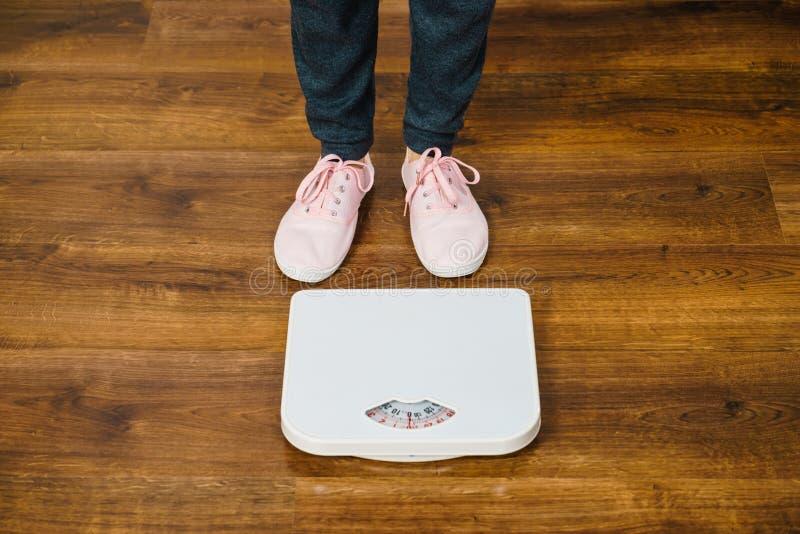 Femme avec les espadrilles roses sur l'échelle de poids de salle de bains image libre de droits