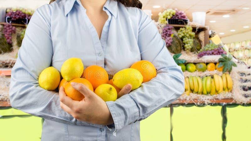 Femme avec les fruits citriques sur le marchand de légumes photos stock