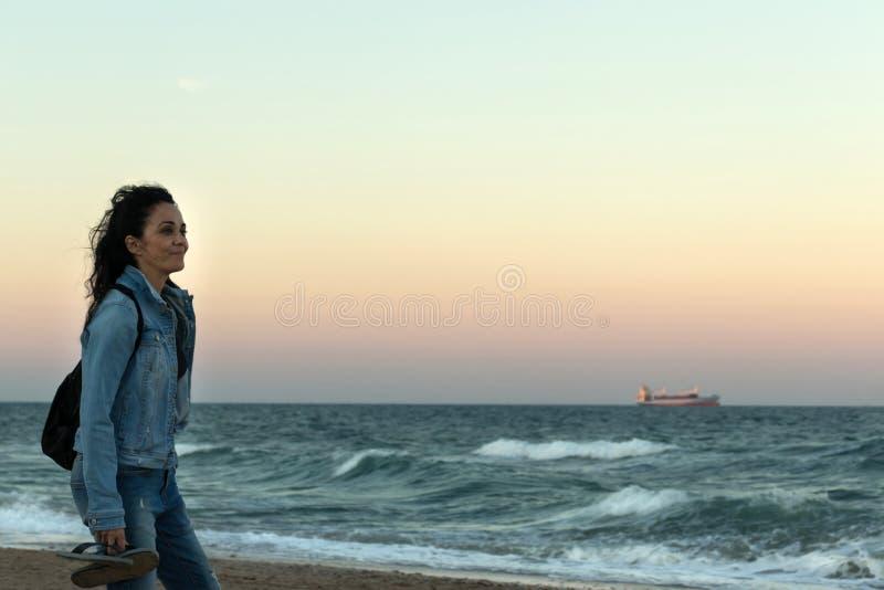 Femme avec les jeans et la veste de denim, observant le coucher du soleil sur la plage photo stock