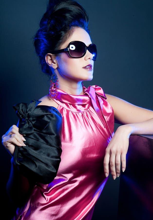 Femme avec les lunettes de soleil et le sac à main de mode photographie stock