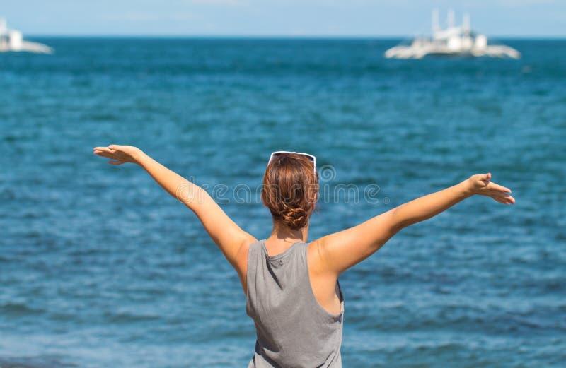 Femme avec les mains augmentées sur le fond de mer Fille heureuse dans le regard occasionnel sur le bord de la mer images stock