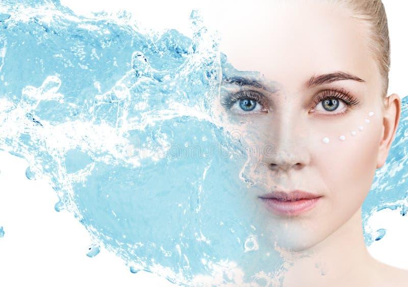Femme avec les points crèmes sur le visage dans l'éclaboussure de l'eau bleue photos stock