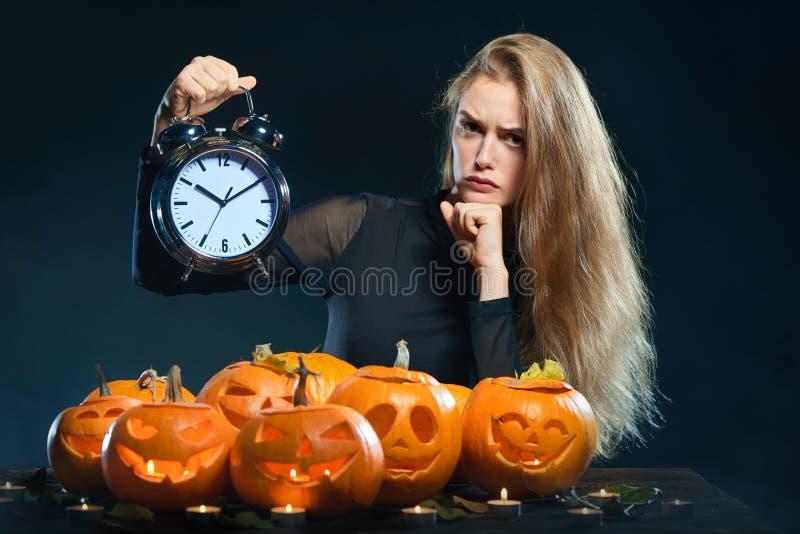 Femme avec les potirons et le réveil de Halloween photos stock