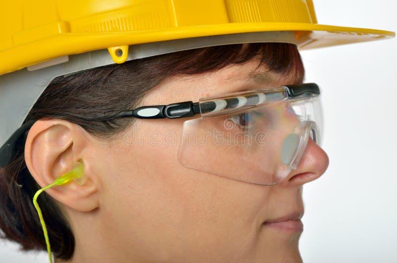 Femme avec les prises protectrices d'oreille photo stock