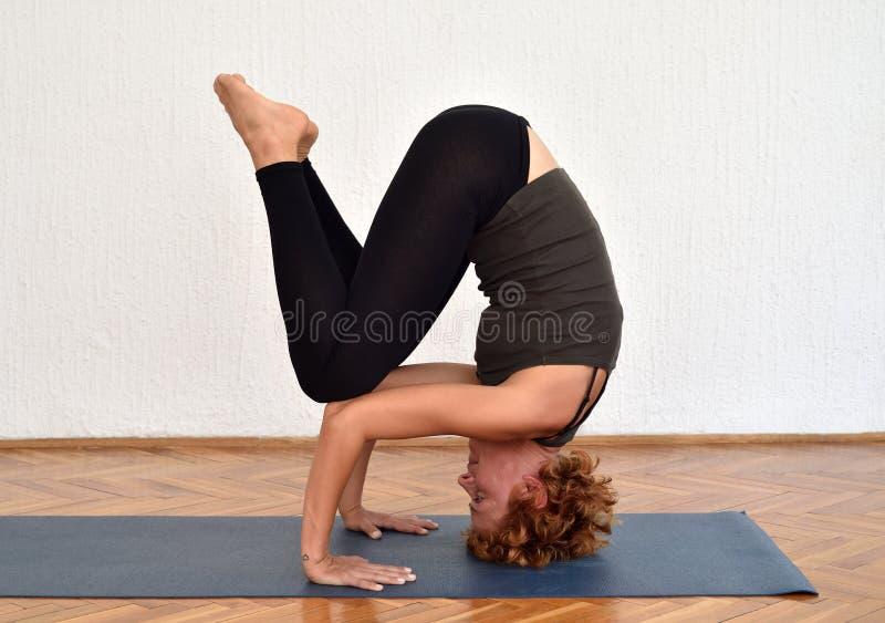 Femme avec les vêtements de sport de port de cheveux courts faisant le yoga à l'intérieur photo stock