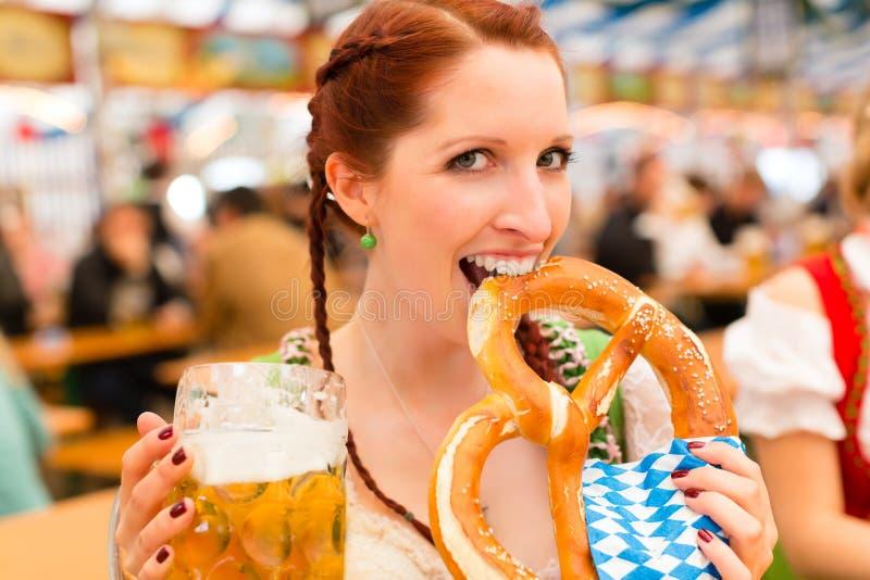 Femme avec les vêtements ou le dirndl bavarois dans la tente de bière photographie stock