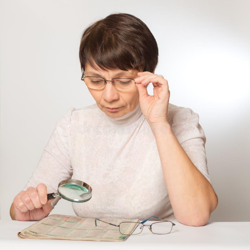 Femme avec les verres et la loupe lisant un journal photos stock