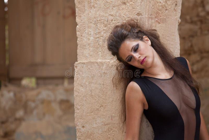Femme avec les yeux fermés au mur photo stock
