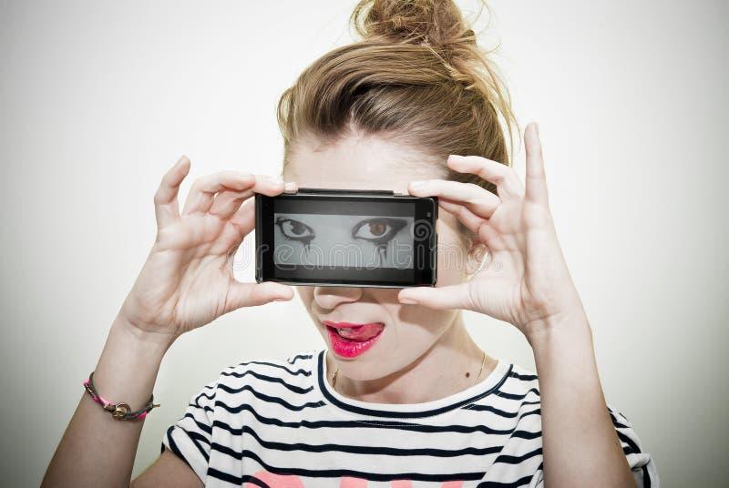 Femme avec les yeux mauvais au téléphone intelligent image stock