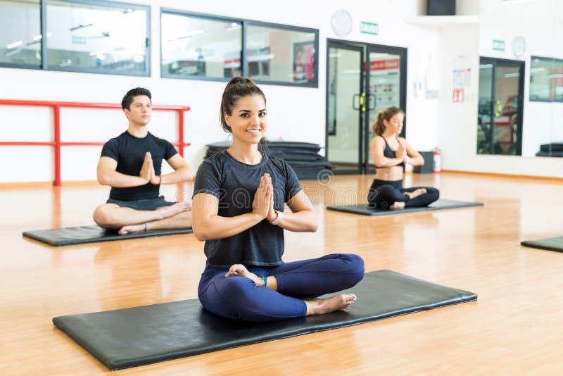 Femme avec méditer étreint par mains avec des amis dans le gymnase images libres de droits