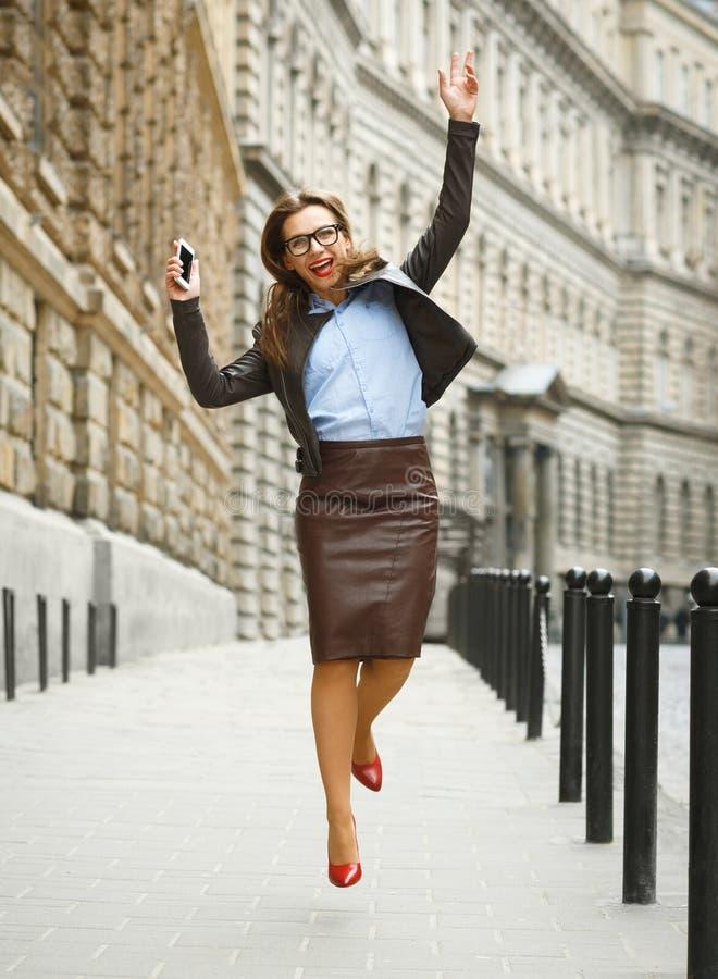 Femme avec plaisir d'affaires sautant pour la joie tout en parlant sur le SM photo libre de droits