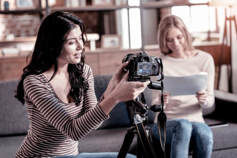 Femme avec plaisir fixant son caméscope images libres de droits