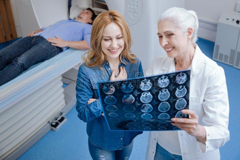 Femme avec plaisir gaie se tenant près de l'oncologiste photos stock