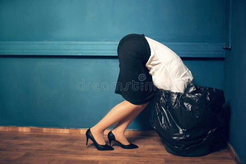 Femme avec sa tête dans la poubelle de déchets photographie stock