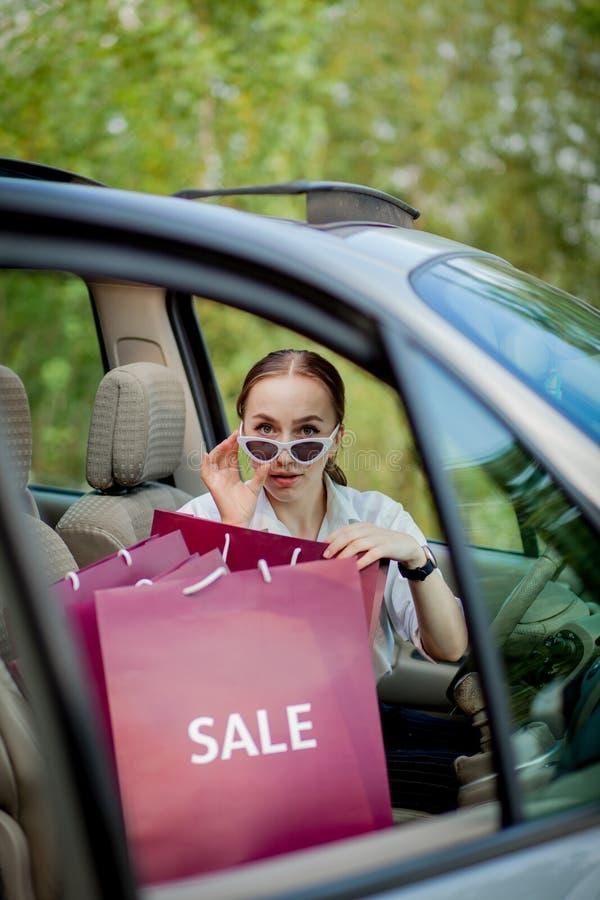 Femme avec ses sacs à provisions dans le concept de achat automobile images libres de droits