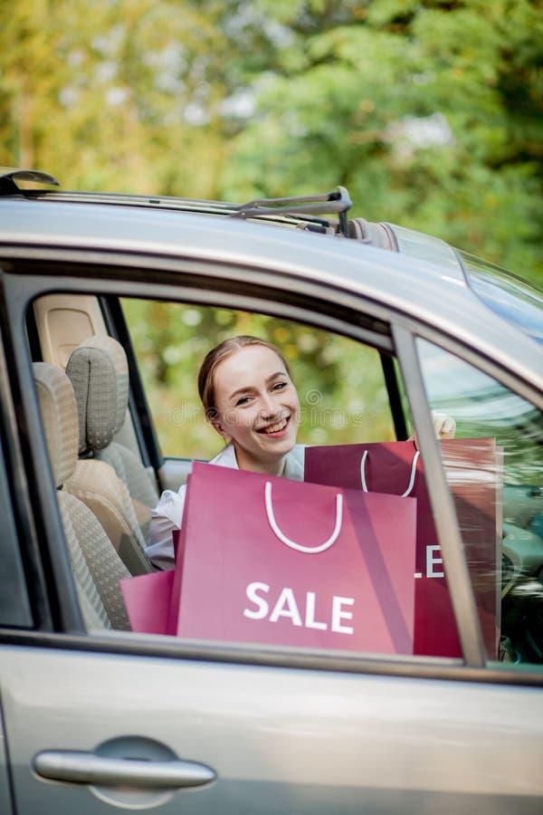 Femme avec ses sacs à provisions dans le concept de achat automobile photo stock