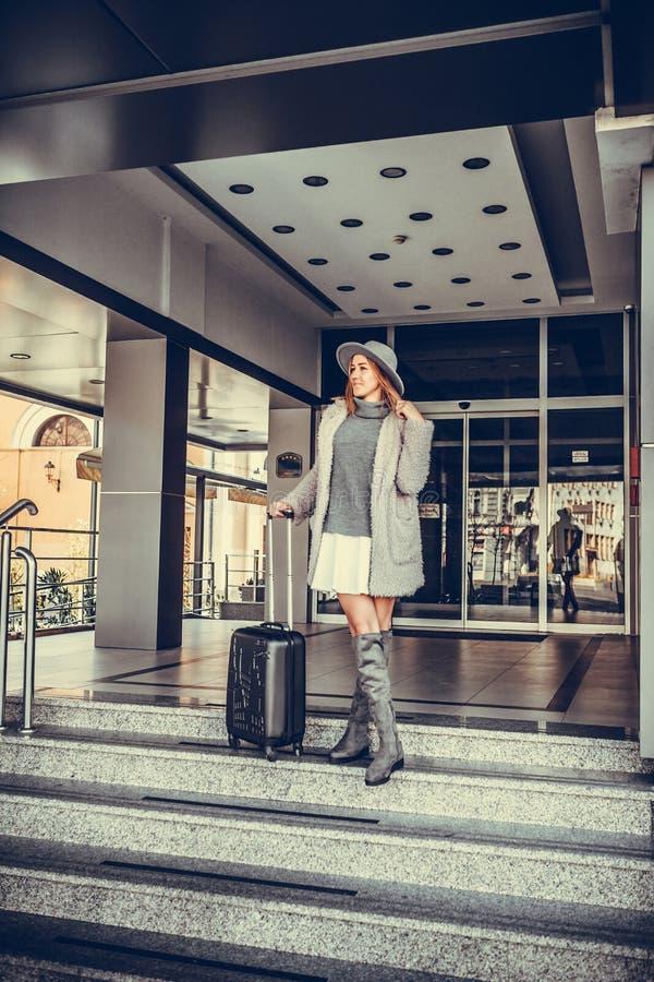 Femme avec un avant de attente de taxi de valise de porte d'hôtel photo libre de droits