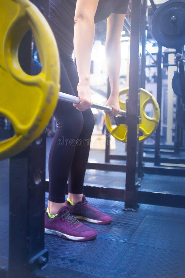 Femme avec un barbell faisant des exercices dans le gymnase photo stock