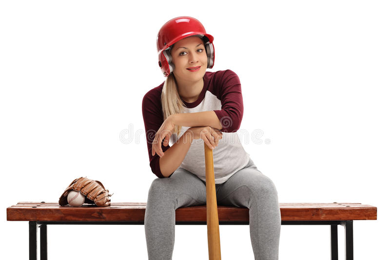 Femme avec un casque et une batte de baseball se reposant sur un banc en bois photos stock