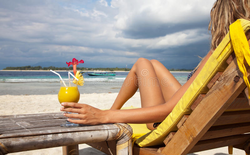 Femme avec un cocktail sur la plage images libres de droits