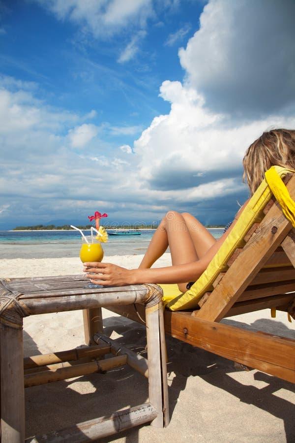 Femme avec un cocktail sur la plage photographie stock libre de droits