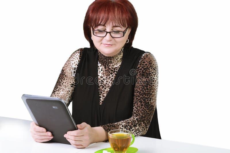 Femme avec un comprimé à la table sur un fond blanc photos libres de droits