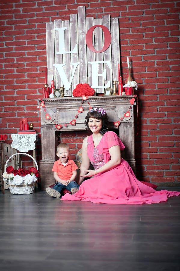 Femme avec un enfant par la cheminée image stock