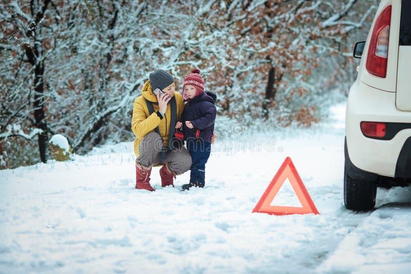 Femme avec un enfant sur la route d'hiver photographie stock libre de droits